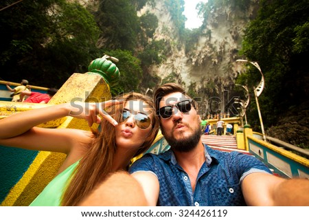 Close-up portrait of beautiful travel couple,wear casual hipster outfit,make selfie of their trip,positive mood,happy couple,couple wear sunglasses,shows tongue,crazy self portrait,emotional people