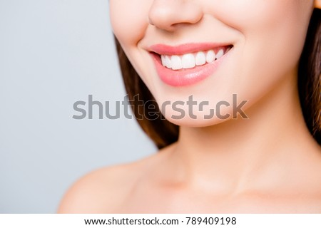 Close up portrait of beautiful wide smile with whitening teeth of young fresh woman isolated over white background, dental care