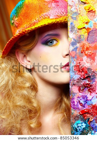 close-up portrait of beautiful woman artist looking from behind of palette