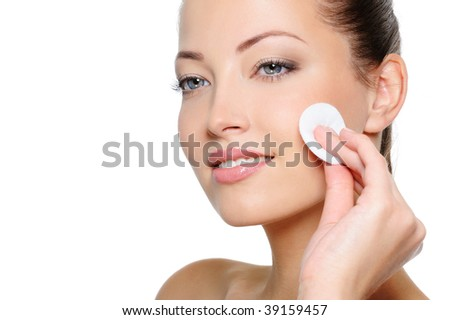 Close-up portrait of beautiful woman cleaning her pretty face with cotton swab