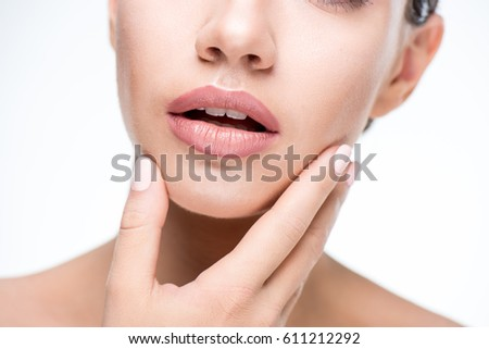 Close up portrait of beautiful woman touching face isolated on white #611212292
