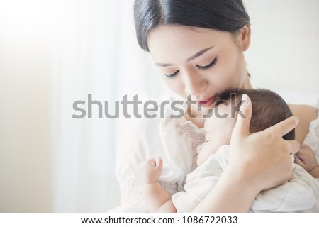 Close up portrait of beautiful young asian mother with her newborn baby, copy space with bed in the hospital background. Healthcare and medical love, lifestyle mother's day concept