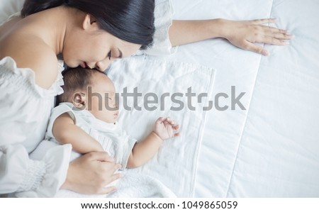 Close up portrait of beautiful young asian or caucasian mother girl kissing her healthy newborn baby sleep in bed with copy space. Healthcare and medical love asia woman lifestyle mother's day concept