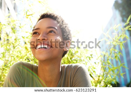 Close up portrait of beautiful young black woman smiling outdoors #623123291