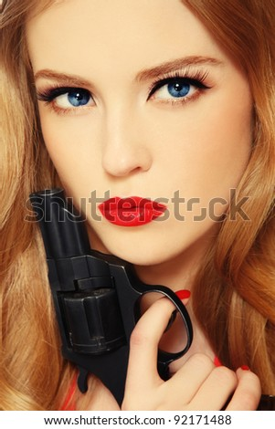 Close-up portrait of beautiful young blond woman with revolver in hand