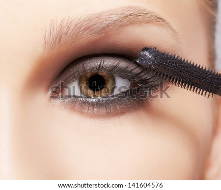 close-up portrait of beautiful young brunette woman applying mascara for eyelash extension