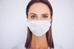 Close up portrait of beautiful young european woman doctor nurse wearing protective mask corona virus prevention. Free space for text mockup banner. Avoid contaminating Corona virus Covid-19 concept