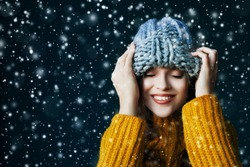 Close up portrait of beautiful young happy smiling girl wearing grey big loop knitted beanie hat, posing on dark blue background. Model closed her eyes. Snowfall.  Copy, empty space for text