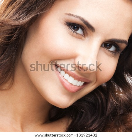 Close up portrait of beautiful young happy smiling woman, isolated over white background