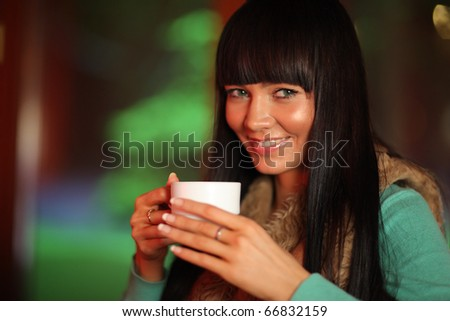 Close-up portrait of beautiful young woman holding cup of tea or coffee. Shallow DOF