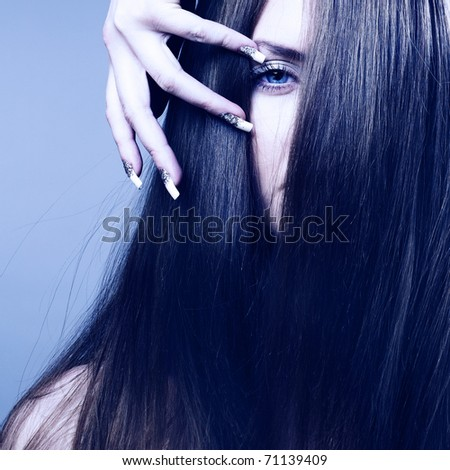 Close-up portrait of beautiful young woman with healthy hair, glamour make-up and manicure