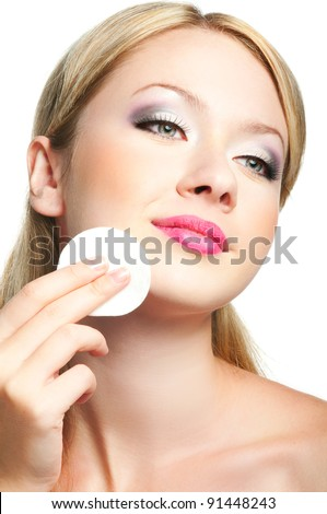 Close-up portrait of beauty young woman cleaning her face