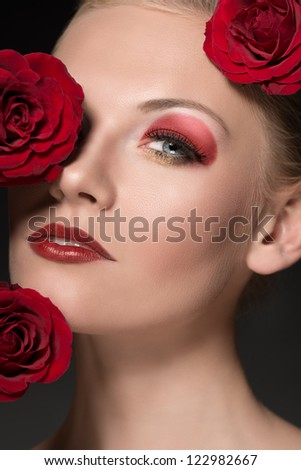 close-up portrait of blonde girl with three red roses near the face, she looks in to the lens with sensual eyes