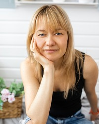 Close-up portrait of blonde, with bangs, landscape designer woman 40-42 years old, looks into the camera, hand under chin, without makeup. smile on face