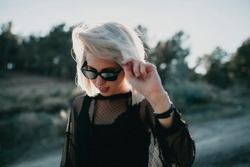 Close up portrait of blonde woman with sunglasses and black dress walking outdoors with sun backlighting.