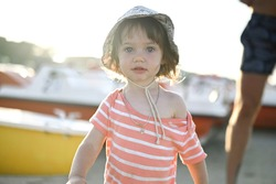 Close up portrait of Blue eyed girl. Lifestyles Small beautiful baby girl walking on the beach in Rimini, Italy. 1 year caucasian baby girl. Family holiday.