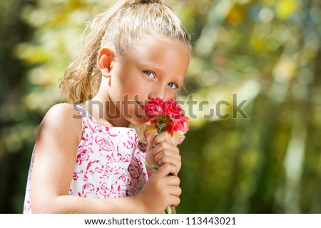 Close up portrait of blue eyed girl smelling flower outdoors.