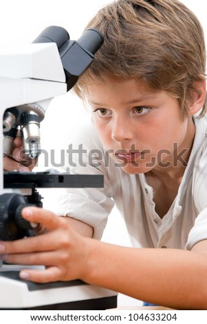 Close up portrait of boy with microscope.Isolated on white.