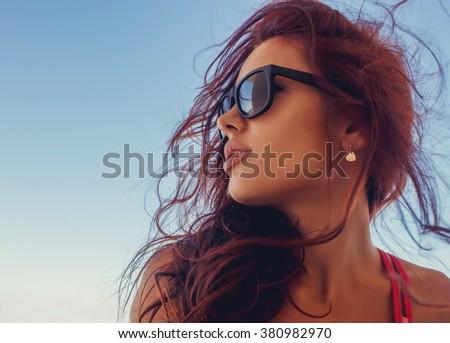 Close up portrait of brunette woman in a sunglasses.