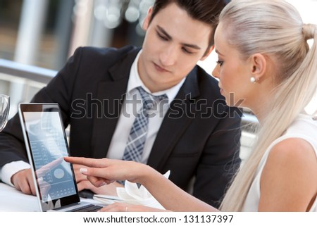 Close up portrait of businesswoman showing information on laptop to partner. - stock photo