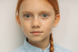 close-up portrait of caucasian surprised red haired girl isolated yellow. adorable shocked child with big blue eyes surprisingly react on something, look at camera. positive emotional child