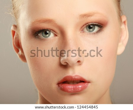 Close-up portrait of caucasian young woman isolated on beige background