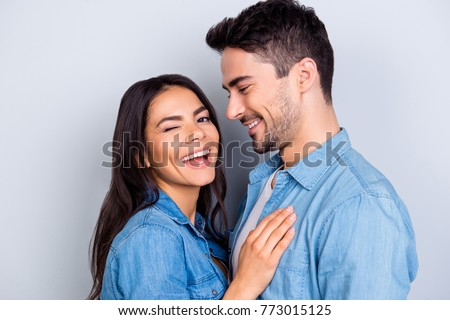 Close up portrait of caucasion lovely couple - smiling man with bristle looking at his funny, cute woman who laugh, blink and looking at camera  standing over grey background