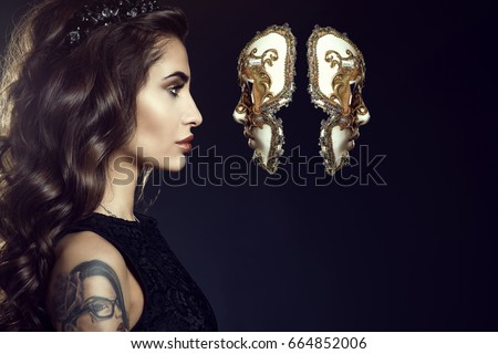 Close up portrait of charming lady with dark wavy silky hair and perfect make-up wearing jewel crown and looking in the face of Venetian mask hanging in the air. Backlight. Copy-space. Studio shot #664852006