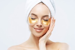 Close up portrait of charming young woman with cosmetic collagen patches under eyes, enjoys flawless of skin, has well cared complexion, manicure, wears wrapped towel on head, stands indoor.