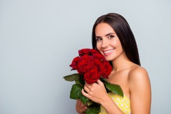 Close up portrait of cheerful attractive beautiful cute lovely woman with straight smooth hair wearing dotted yellow dress, cuddling roses to the face, isolated on grey background, copy space
