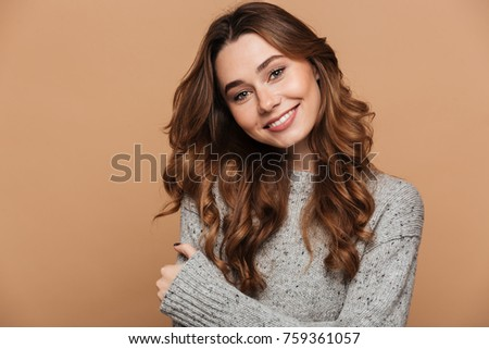 Close-up portrait of cheerful brunette woman in gray knitted sweater looking at camera, isolated on beige background
