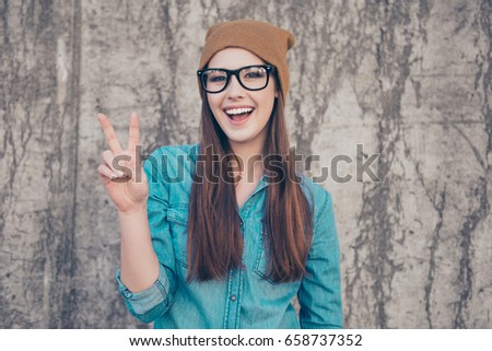 Close up portrait of cheerful playful girl, who is gesturing peace sign and smiles. She is wearing casual clothes, glasses and a brown hat, walking outdoors near concrete wall