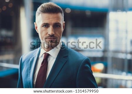 Close up portrait of chic adult man standing in business center and look in camera, making serious face #1314579950