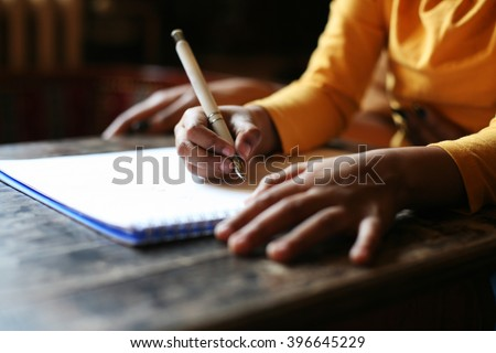 Close up portrait of child's hands writing.