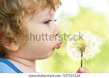 Close-up portrait of child with dandelion on sunny-green background