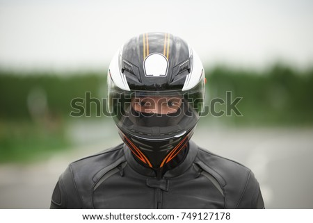 Close up portrait of confident handsome young motorbiker wearing stylish helmet and leather jacket staring at camera with eyes full of determination, ready for motor race on summer day outdoors.