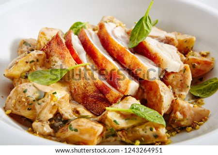 Close-up portrait of cream potato with pork slices close up. Studio picture of delicious dish served on plate. Restaurant meal concept