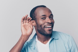 Close up portrait of curious interested delightful funny amazed cheerful surprised african man holding hand near ear and trying to hear the information isolated on gray background