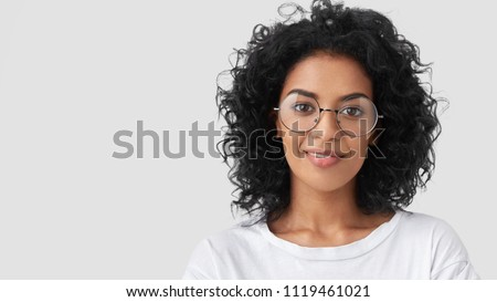 Close up portrait of curly female adult has charming smile, curly dark hair, wears big glasses, satisfied as finished domestic work earlier, being successful designer or architect, has talent
