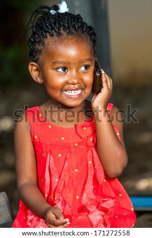 Close up portrait of cute african girl having conversation on smart phone outdoors.