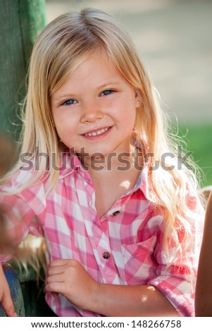 Close up portrait of cute blond girl outdoors.