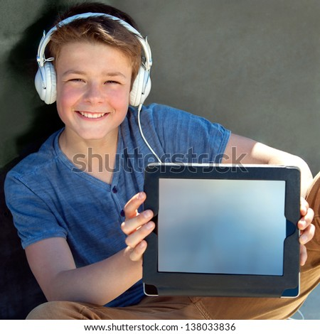 Close up portrait of cute boy showing blank tablet screen.