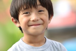 close up portrait of cute boy smiling in the park
