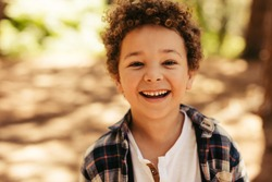 Close up portrait of cute boy smiling outdoors. Kid looking at camera and laughing.