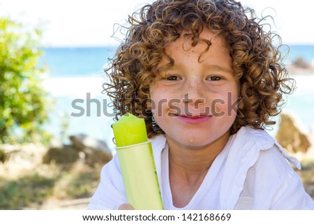 Close up portrait of cute boy with curly hair eating ice pop outdoors.