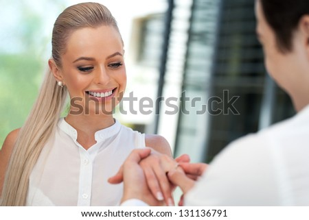 Close up portrait of cute girl being surprised with diamond ring on date.