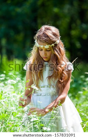 Close up portrait of cute girl picking flowers in field.
