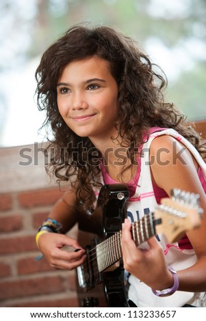 Close up portrait of cute girl playing guitar indoors.