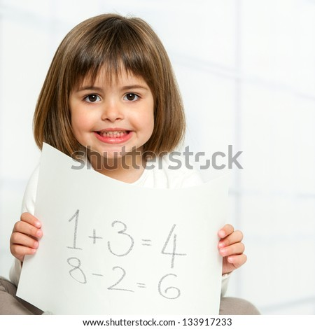 Close up portrait of cute girl showing maths equations on paper.