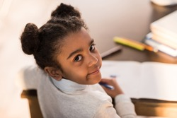 Close-up portrait of cute little african american girl drawing with felt tip pens, doing homework concept